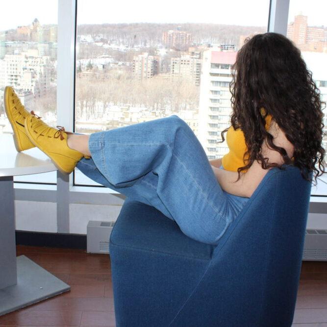fille aux longs cheveux bouclés porte un jean avec de jolis chaussons jaunes